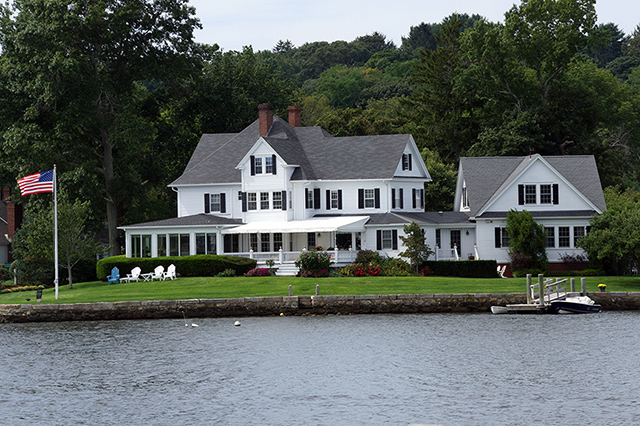 Large home on the water with American flag on lawn