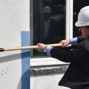 Man wielding a sledgehammer to help with the demolition of the building at 366 West Putnam Ave in Greenwich